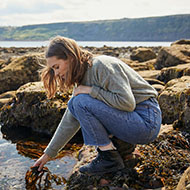 Woman on beach rock pooling by Dependable