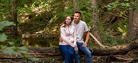 Couple sitting on log in woodland by Dependable