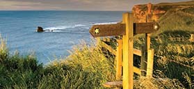 Stile and sign on the coast