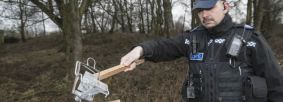 An officer demonstrates the power of an illegal pole trap