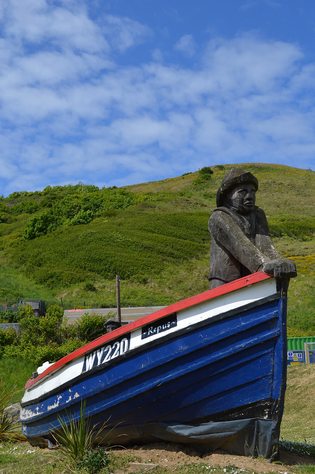 Repus restored fishing coble with carved fisherman, Skinningrove